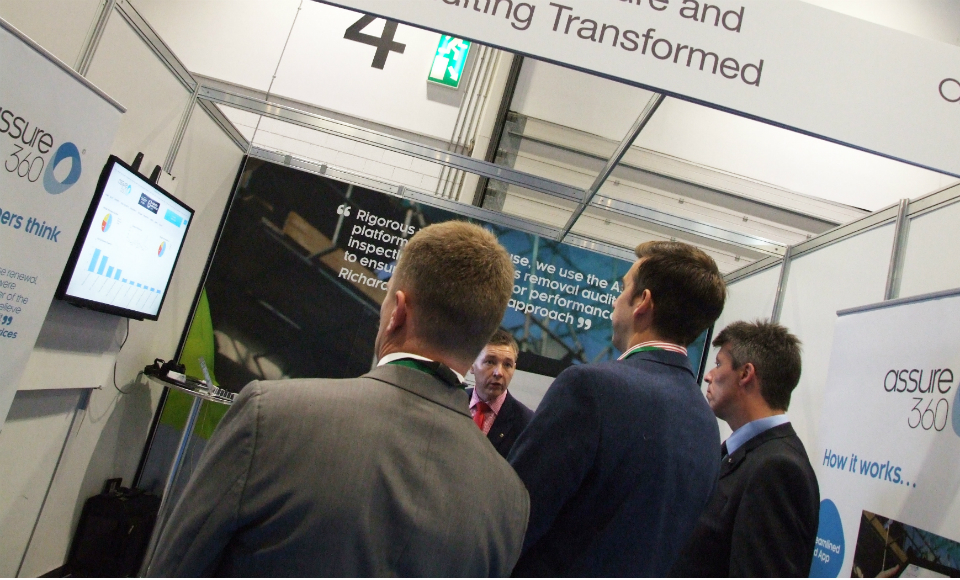 A group of delegates huddle round the Assure360 stand at Expo