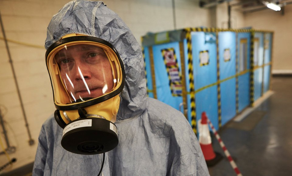 An asbestos analyst wears protective gear prior to beginning a four-stage clearance inspection